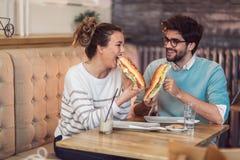 Χαριτωμένο νέο ζεύγος περνώντας καλά μαζί και τρώγοντας τα τρόφιμα στον καφέ Στοκ Εικόνες