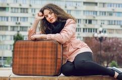 Χαριτωμένο νέο κορίτσι με την αναδρομική βαλίτσα που σκέφτεται για τα ταξίδια στη μεγάλη οδό πόλεων Στοκ φωτογραφία με δικαίωμα ελεύθερης χρήσης