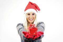 Χαριτωμένο νέο κορίτσι με το καπέλο Άγιου Βασίλη, που κρατά ένα παρόν Στοκ Εικόνα