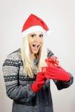 Χαριτωμένο νέο κορίτσι με το καπέλο Άγιου Βασίλη, που κρατά ένα παρόν Στοκ φωτογραφίες με δικαίωμα ελεύθερης χρήσης