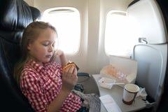 Χαριτωμένο νέο κορίτσι που έχει το γεύμα στο αεροπλάνο πετώντας Στοκ φωτογραφίες με δικαίωμα ελεύθερης χρήσης