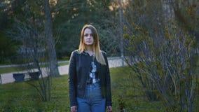 Χαριτωμένο νέο κορίτσι που στέκεται στο πάρκο και να κοιτάξει επίμονα κεκλεισμένων των θυρών στοκ φωτογραφία με δικαίωμα ελεύθερης χρήσης