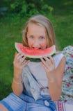 Χαριτωμένο νέο κορίτσι που τρώει το καρπούζι στη χλόη στο καλοκαίρι Στοκ εικόνα με δικαίωμα ελεύθερης χρήσης