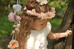 Χαριτωμένο νέο κορίτσι που φορά ένα φόρεμα άνοιξη και ένα στεφάνι της ταλάντευσης λουλουδιών Στοκ φωτογραφία με δικαίωμα ελεύθερης χρήσης