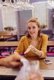 Χαριτωμένο νέο κορίτσι που χαμογελά στον μπάρμαν επισκεμμένος το φραγμό στοκ φωτογραφίες με δικαίωμα ελεύθερης χρήσης