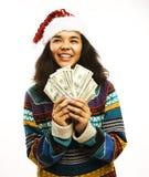 Χαριτωμένο νέο κορίτσι santas καπέλο με τα χρήματα που απομονώνεται στο κόκκινο Στοκ Εικόνα