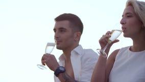 Χαριτωμένο νέο κρασί κατανάλωσης ζευγών στο ηλιοβασίλεμα Φίλος και φίλη ερωτευμένοι απόθεμα βίντεο