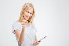 Χαριτωμένο νέο ξανθό κορίτσι που δείχνει στο σημειωματάριο εκμετάλλευσης καμερών Στοκ φωτογραφίες με δικαίωμα ελεύθερης χρήσης