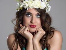 Χαριτωμένο νέο σκεπτικό πρότυπο φορώντας floral στεφάνι ομορφιάς με το κεφάλι στα χέρια που ανατρέχουν Στοκ Εικόνα