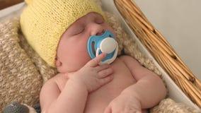 Χαριτωμένο νεογέννητο μωρό στους πλεκτούς ύπνους καπέλων σε ένα λίκνο με το ομοίωμα απόθεμα βίντεο
