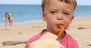 Χαριτωμένο νερό καρύδων κατανάλωσης παιδιών στην παραλία φιλμ μικρού μήκους