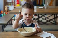 Χαριτωμένο ξανθό αγόρι μικρών παιδιών που τρώει τις μπουλέττες στο εσωτερικό στο εστιατόριο Υγιή, ανθυγειινά τρόφιμα για τα παιδά στοκ φωτογραφίες