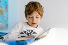 Χαριτωμένο ξανθό αγόρι παιδάκι στις πυτζάμες που διαβάζει το βιβλίο στην κρεβατοκάμαρά του Συγκινημένη ανάγνωση παιδιών δυνατή, κ στοκ φωτογραφίες με δικαίωμα ελεύθερης χρήσης