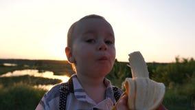 Χαριτωμένο ξανθό αγόρι που τρώει την μπανάνα στο πάρκο στο ηλιοβασίλεμα σε σε αργή κίνηση φιλμ μικρού μήκους
