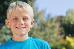Χαριτωμένο ξανθό αγόρι που χαμογελά στη κάμερα Στοκ Φωτογραφίες