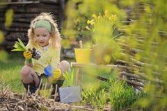 Χαριτωμένο ξανθό κορίτσι παιδιών που έχει τη διασκέδαση που παίζει λίγο κηπουρό Στοκ εικόνες με δικαίωμα ελεύθερης χρήσης