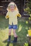 Χαριτωμένο ξανθό κορίτσι παιδιών που έχει τη διασκέδαση που παίζει λίγο κηπουρό Στοκ Εικόνα