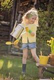Χαριτωμένο ξανθό κορίτσι παιδιών που έχει τη διασκέδαση που παίζει λίγο κηπουρό Στοκ Εικόνες