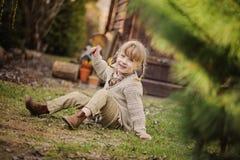 Χαριτωμένο ξανθό κορίτσι παιδιών που έχει τη διασκέδαση στον πρόωρο κήπο άνοιξη Στοκ εικόνες με δικαίωμα ελεύθερης χρήσης