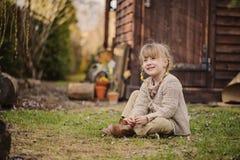 Χαριτωμένο ξανθό κορίτσι παιδιών που έχει τη διασκέδαση στον πρόωρο κήπο άνοιξη Στοκ Εικόνα