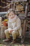 Χαριτωμένο ξανθό κορίτσι παιδιών που έχει τη διασκέδαση στον πρόωρο κήπο άνοιξη Στοκ Εικόνες