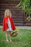 Χαριτωμένο ξανθό κορίτσι παιδιών που παίζει λίγη κόκκινη οδηγώντας κουκούλα στο θερινό κήπο Στοκ φωτογραφία με δικαίωμα ελεύθερης χρήσης