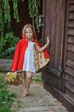 Χαριτωμένο ξανθό κορίτσι παιδιών που παίζει λίγη κόκκινη οδηγώντας κουκούλα στο θερινό κήπο Στοκ εικόνες με δικαίωμα ελεύθερης χρήσης