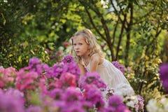 Χαριτωμένο ξανθό κορίτσι παιδιών στον ανθίζοντας θερινό κήπο Στοκ Εικόνα
