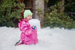 Χαριτωμένο ξανθό κορίτσι που κρατά μια τεράστια χιονιά Στοκ Φωτογραφίες