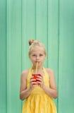 Χαριτωμένο ξανθό κορίτσι που πίνει την κόκκινη λεμονάδα Στοκ φωτογραφία με δικαίωμα ελεύθερης χρήσης