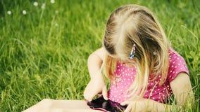 Χαριτωμένο ξανθό κορίτσι στην προσχολική συνεδρίαση ηλικίας στο πράσινο παιχνίδι χλόης με το έξυπνο τηλέφωνο φιλμ μικρού μήκους
