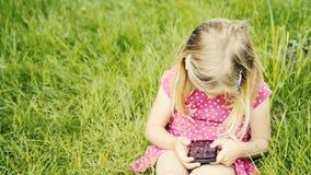 Χαριτωμένο ξανθό κορίτσι στην προσχολική συνεδρίαση ηλικίας στο πράσινο παιχνίδι χλόης με το έξυπνο τηλέφωνο απόθεμα βίντεο