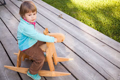 Χαριτωμένο ξανθό κοριτσάκι που οδηγά το ξύλινο άλογο Στοκ Εικόνες