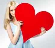 Χαριτωμένο ξανθό κρύψιμο κοριτσιών πίσω από την καρδιά Στοκ Φωτογραφίες