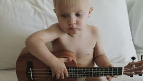 Χαριτωμένο ξανθό παιδί που παίζει ukulele απόθεμα βίντεο