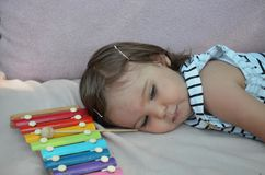 Χαριτωμένο ξανθό παιχνίδι παιδιών με το xylophone στο σπίτι Έννοια δημιουργικότητας και εκπαίδευσης στοκ φωτογραφία με δικαίωμα ελεύθερης χρήσης