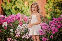 Χαριτωμένο ξανθό παιχνίδι κοριτσιών παιδιών στο θερινό ανθίζοντας κήπο Στοκ Εικόνα