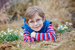 Χαριτωμένο ξανθό προσχολικό αγόρι παιδιών που ανακαλύπτει τα πρώτα λουλούδια άνοιξη, όμορφα snowdrops Στοκ Εικόνες