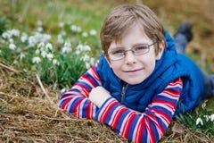 Χαριτωμένο ξανθό προσχολικό αγόρι παιδιών που ανακαλύπτει τα πρώτα λουλούδια άνοιξη, όμορφα snowdrops Στοκ Φωτογραφία