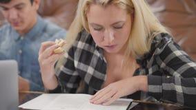 Χαριτωμένο ξανθό σημειωματάριο ανάγνωσης κοριτσιών πορτρέτου που τρώει το σάντουιτς ενώ ο φίλος της που ερευνά τις πληροφορίες γι απόθεμα βίντεο