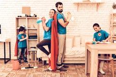 Χαριτωμένο οικογενειακό καθαρίζοντας σπίτι Superhero με τα παιδιά στοκ φωτογραφίες