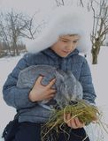 Χαριτωμένο παιδί καπέλων χαμόγελου μωρών εποχής πάρκων φύσης προσώπου κουνελιών υπαίθριο υπαίθρια λίγο λευκό αγόρι παιδιών χειμερ Στοκ Εικόνες