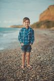 Χαριτωμένο παιδί παιδιών αγοριών που φορά το μοντέρνο πουκάμισο και το ξυπόλυτο θέτοντας τρέξιμο τζιν παντελόνι στην παραλία πετρ Στοκ Φωτογραφίες