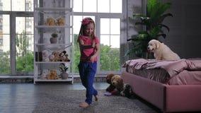 Χαριτωμένο παιδί που χορεύει για τη συνεδρίαση κουταβιών στο κρεβάτι απόθεμα βίντεο