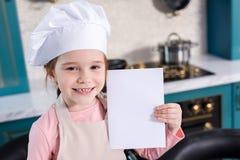 χαριτωμένο παιδί στο καπέλο αρχιμαγείρων και ποδιών κάρτα και το χαμόγελο εκμετάλλευσης την κενή στοκ φωτογραφία