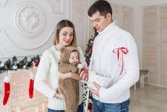 Χαριτωμένο παιδί στο κοστούμι αρκούδων και οι θαυμάσιοι γονείς τους που στέκονται μαζί κοντά στις διακοσμήσεις Χριστουγέννων Στοκ Φωτογραφία
