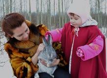 Χαριτωμένο παιδί χιονιού λαγών κουνελιών υπαίθρια λίγη δύο γονέων παιδική ηλικία που χαμογελά οικογένεια CH χειμερινών μωρών γυνα Στοκ Φωτογραφίες