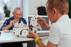 Χαριτωμένο παιχνίδι αγοριών της Νίκαιας με ένα ρομπότ Στοκ εικόνα με δικαίωμα ελεύθερης χρήσης