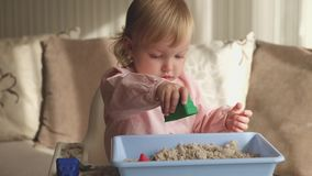 Χαριτωμένο παιχνίδι κοριτσάκι με την κινητική άμμο στο σπίτι Παιχνίδι κάστρων άμμου φιλμ μικρού μήκους