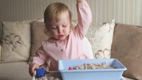 Χαριτωμένο παιχνίδι κοριτσάκι με την κινητική άμμο στο σπίτι Παιχνίδι κάστρων άμμου απόθεμα βίντεο